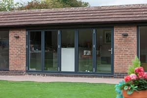 Grey aluminium bi-folding doors closed in a garden room. Highseal Manufacturing manufactures quality pvc and aluminium windows, doors and conservatories and are suppliers of composite doors to the trade, DIY, retail and commercial.