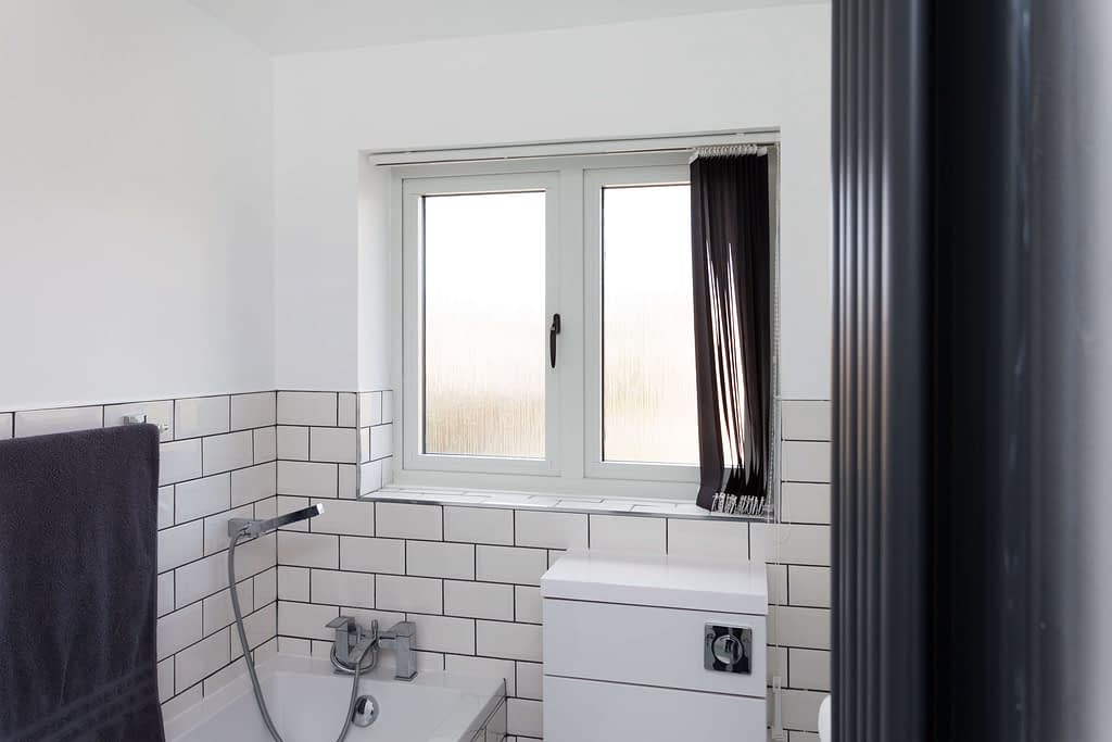 image showing an internal white casement window inside a bathroom with black handles and a flush sash. Windows manufactured by Highseal Manufacturing and installed in Scotland. Showing the toilet and bath in the image.