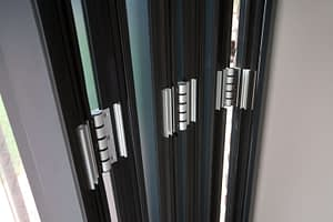 Aluminium bi-folding door stacked showing the hinges. Highseal Manufacturing manufactures quality pvc and aluminium windows, doors and conservatories and are suppliers of composite doors to the trade, DIY, retail and commercial.