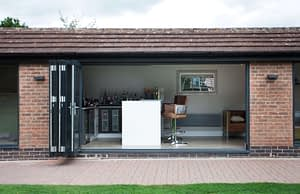 Aluminium bi-folding door installed in a garden room showing the doors stacked up, looking into the room. Highseal Manufacturing manufactures quality pvc and aluminium windows, doors and conservatories and are suppliers of composite doors to the trade, DIY, retail and commercial.