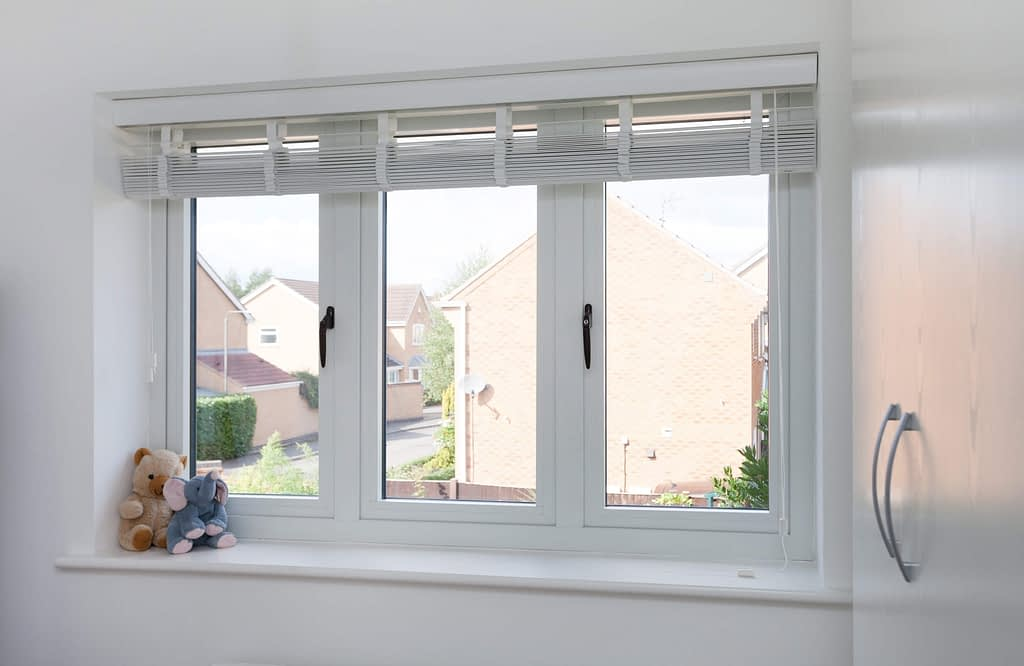 White casement windows with black handles and flush sash, showing the internal view of the window in a bedroom with two openers. Image of the window taken straight on from the left hand side showing the road outside the window. Windows manufactured by Highseal Manufacturing and installed in Scotland.