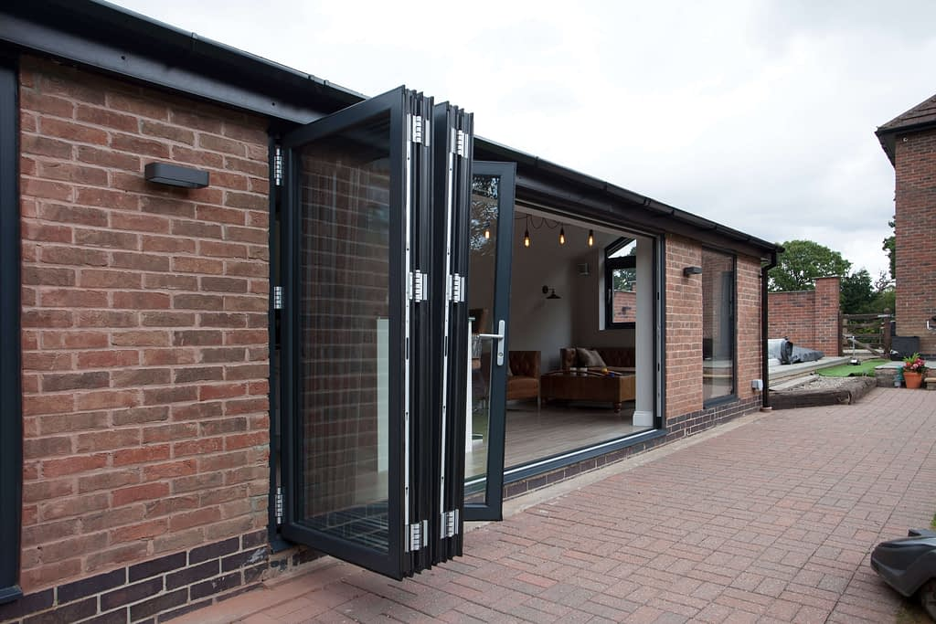 Aluminium grey bi-folding door showing the sashes stocked and inline. Highseal Manufacturing manufactures quality pvc and aluminium windows, doors and conservatories and are suppliers of composite doors to the trade, DIY, retail and commercial.