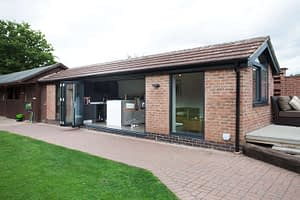 Grey aluminium bi-folding doors fitted in a garden room showing them open and stacked. Highseal Manufacturing manufactures quality pvc and aluminium windows, doors and conservatories and are suppliers of composite doors to the trade, DIY, retail and commercial.