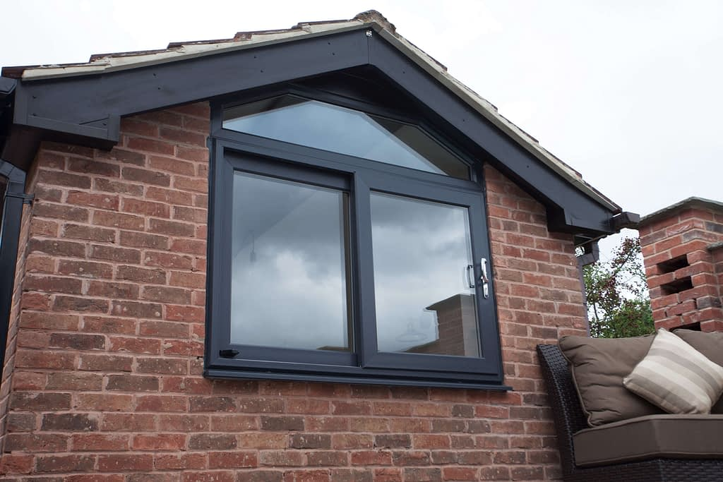 Aluminium grey shaped window with sliding opener. Highseal Manufacturing manufactures quality pvc and aluminium windows, doors and conservatories and are suppliers of composite doors to the trade, DIY, retail and commercial.