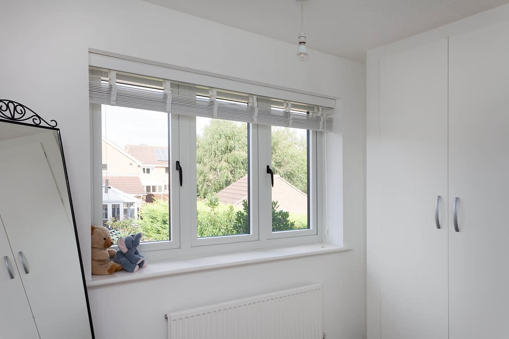 White casement windows with black handles and flush sash, showing the internal view of the window in a bedroom with two openers. Windows manufactured by Highseal Manufacturing and installed in Scotland.